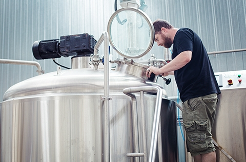Brewer from Boneface checks brewing equipment