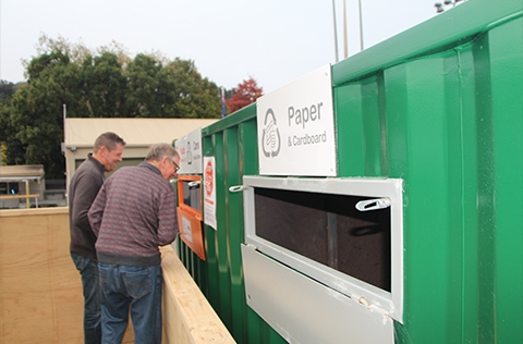 People looking at a waste and recycling station